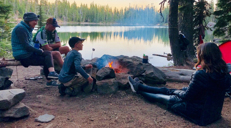 A family sitting around a campfire, roasting marshmallows, next to a tent and a lake