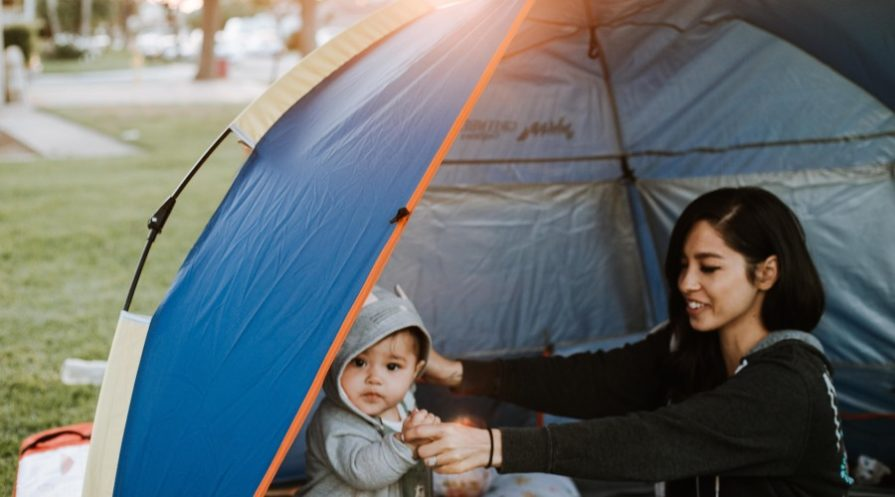 A woman sitting in a tent with a young child