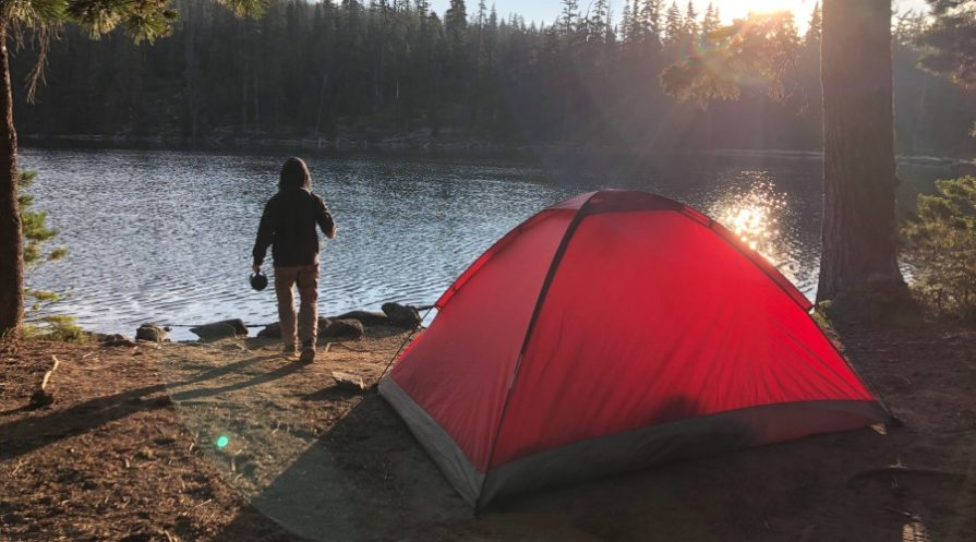 A man walking outdoors on the edge of a lake next to a tent