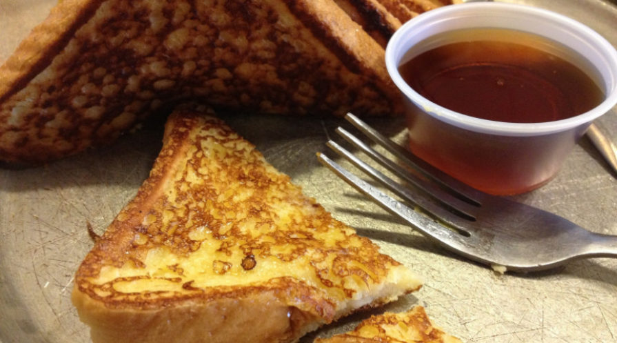 Frech toast with fork and dipping cup for syrup