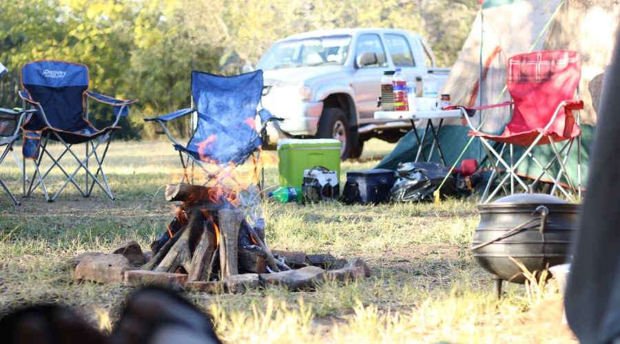 A campsite with the campfire burning, surrounded with camp chairs, a tent and other camping gear