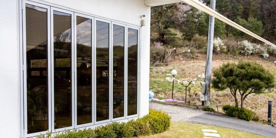 White folding doors behind grassy lawn
