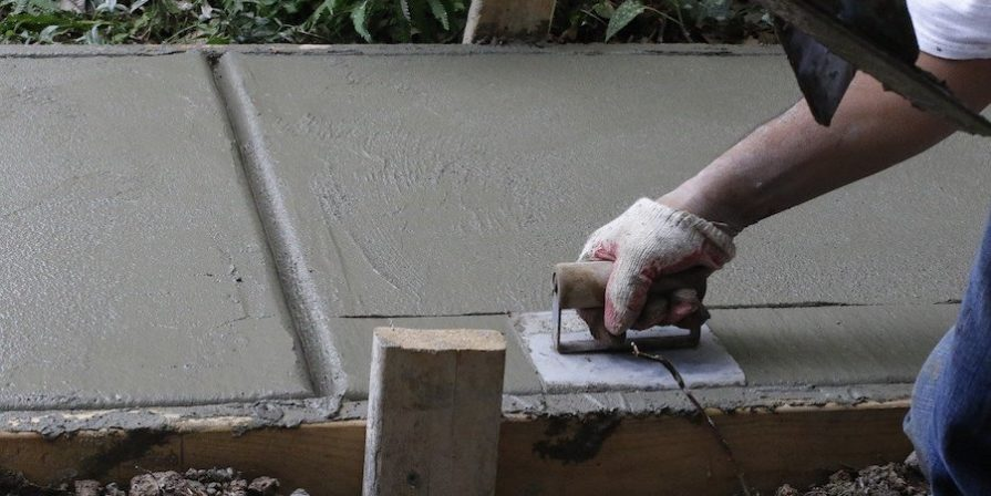 Hand using a trowel to smooth concrete