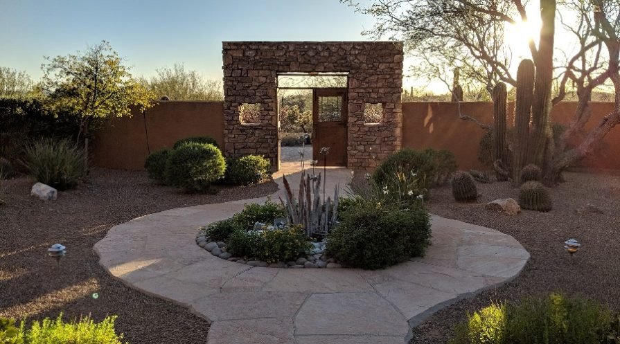 Xeriscaped area with patio pavers and squared arch doorway at end of path