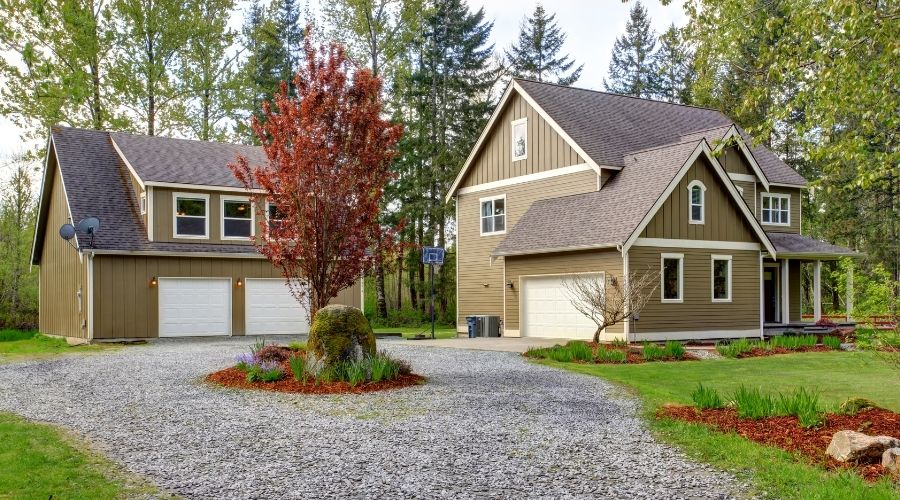 a house and detached garage with a gravel driveway wrapping around a center garden with a tree