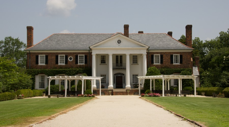 a brick house with columns at the front door and a pergola on each side of the driveway