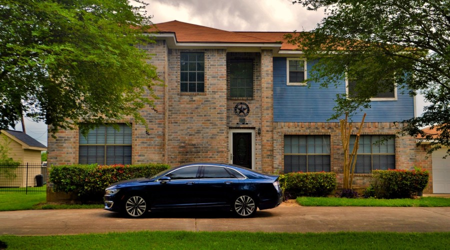 a car parked in front of a house next to manicured shrubs