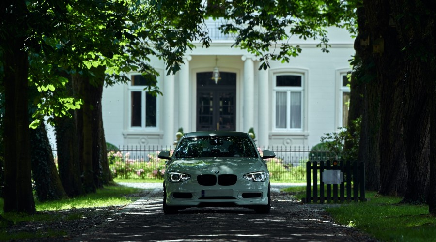a car driving up a driveway away from a house under a canopy of trees