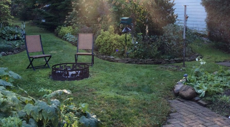 Firepit with seating by path and distinct garden spaces