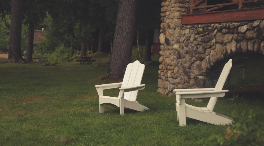 two Adirondack chairs sitting in the front yard by a stone house