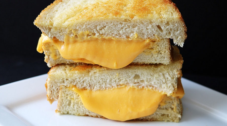grilled cheese sandwich halves stacked on white plate