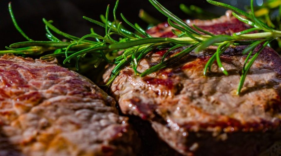 Grilled or broiled meat with herbs on top