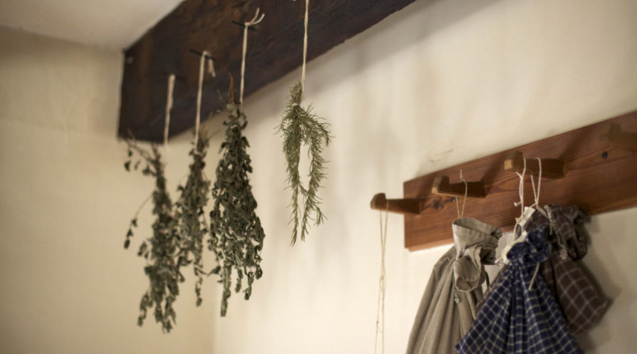 Herbs hang drying from a wooden rack
