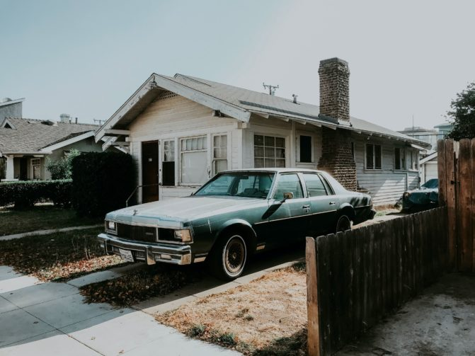 A car standing on the grass and concrete driveway