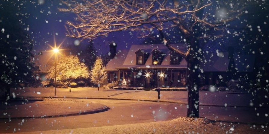 House at night in snowy neighbourhod