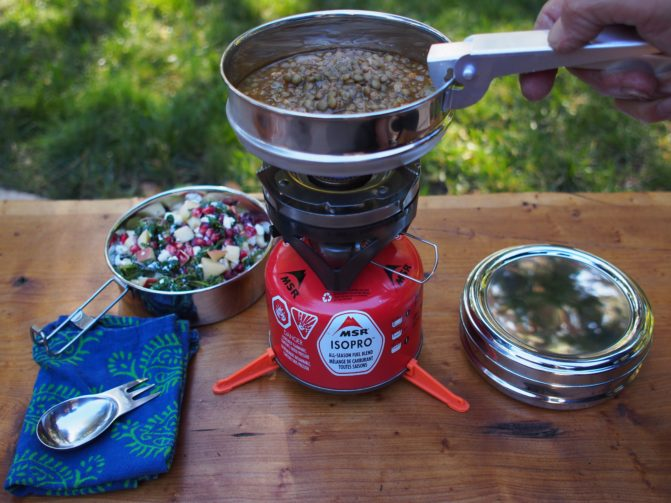 A person making food on a red camping stove