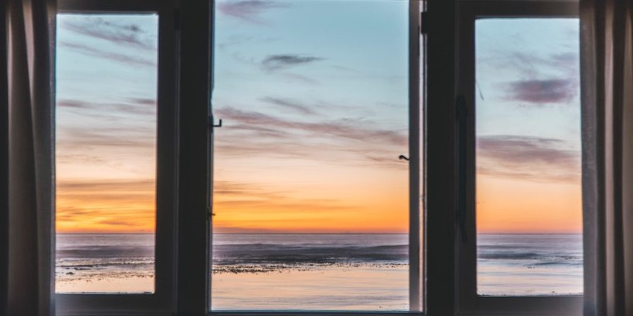 View through a window of sunset over the ocean