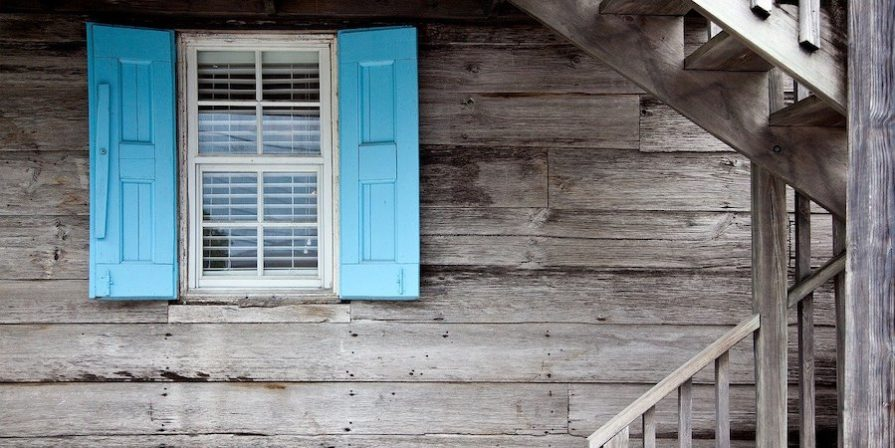 White window with blue shutters on wooden wall