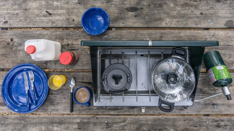 Camping stove on a table with eating items
