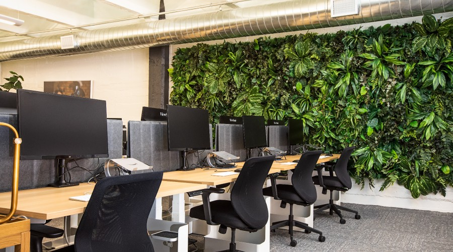 a living wall inside an office building next to a row of computers