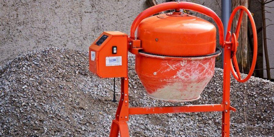 Orange cement mixer in front of gravel