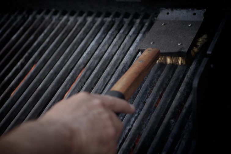 A person cleaning the grill