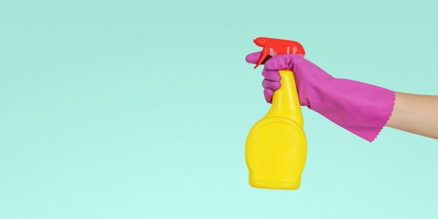 Hand wearing pink glove holding yellow spray bottle