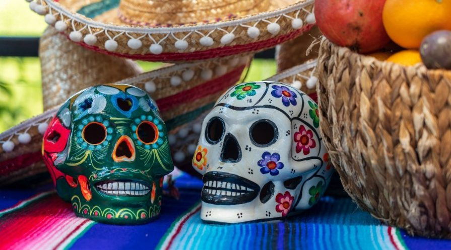 Day of the dead decorated skulls sitting on Mexican blanket