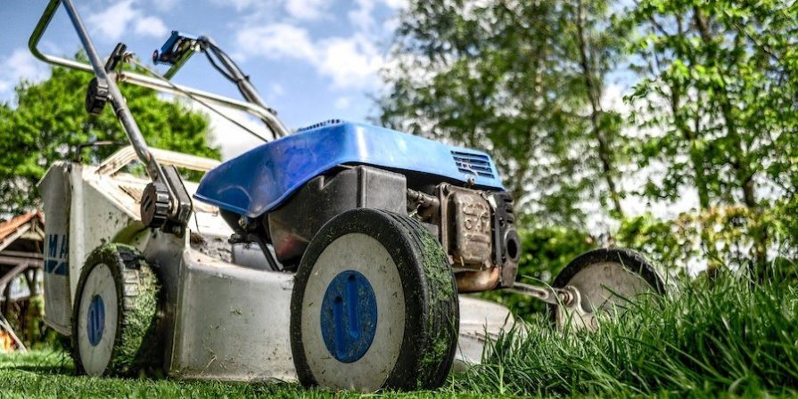 Blue and black lawnmower mowing the lawn