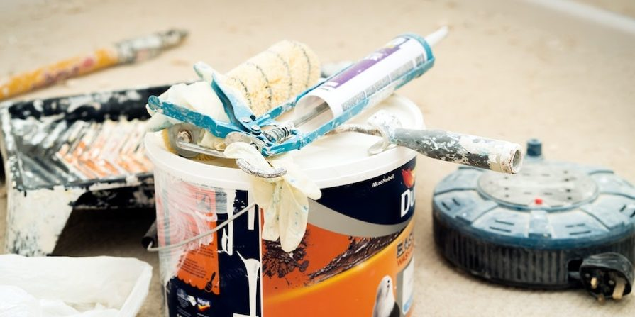 Orange bucket with caulking and other waterproofing equipment