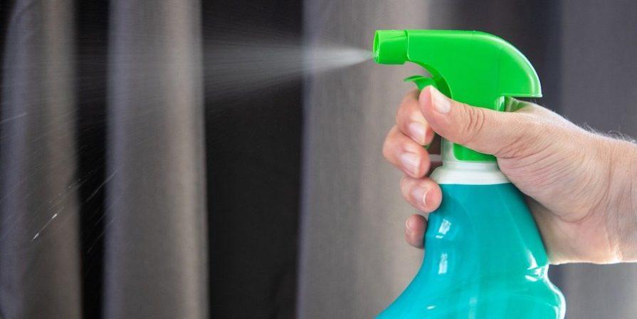 Hand using spray bottle