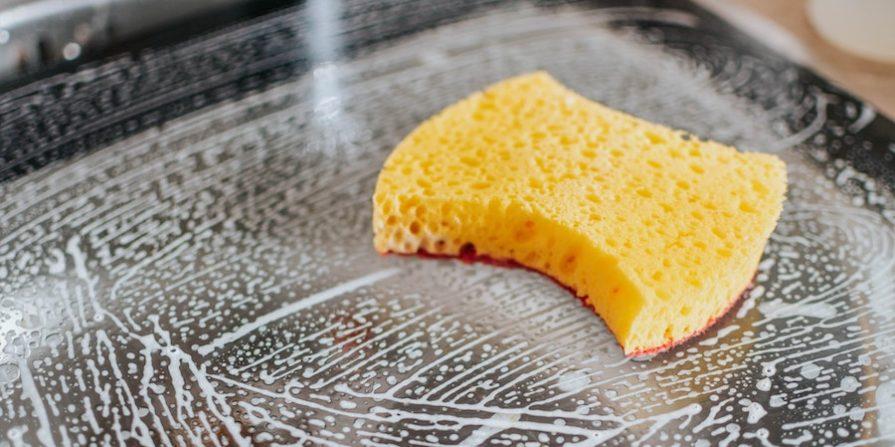 Yellow soapy sponge washing black surface