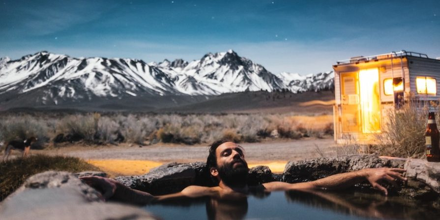 Man in hot tub in front of snowy mountain