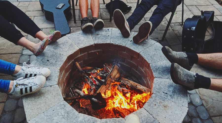 people's feet and guitar cases around the fire pit