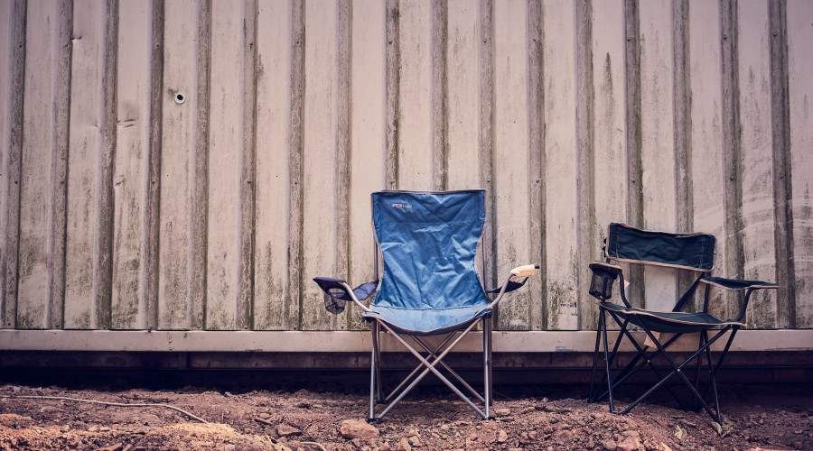 two camping foldup chairs sitting against a wall outdoors