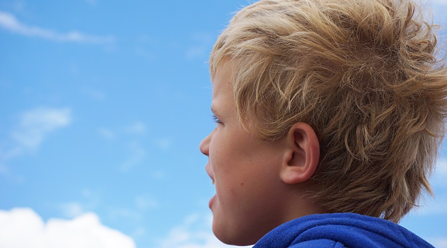 young child looking up into the clouds