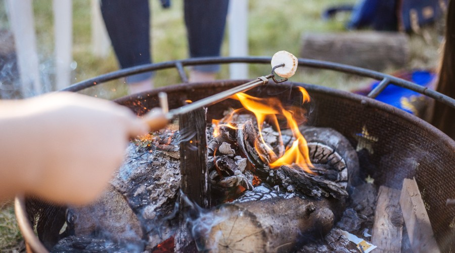 firpit table with someone roasting a marshmallow