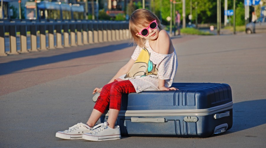 young girl sitting on a suitcase outside