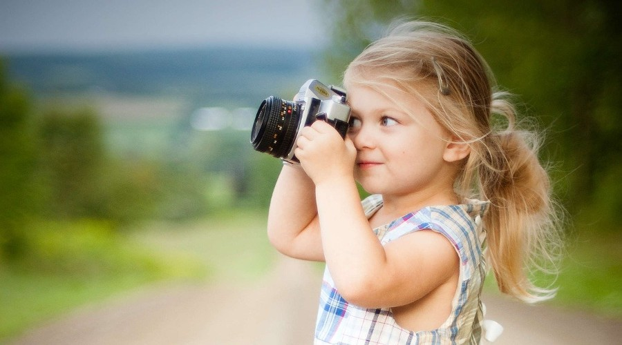 young girl holding camera to her eye