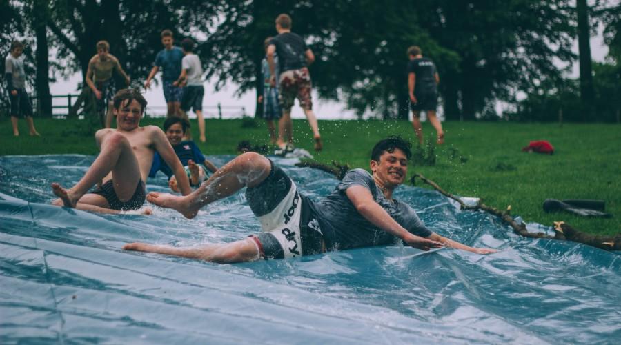 group of men sliding on blue plastic