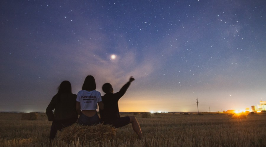 three people sitting outdoors looking at stars