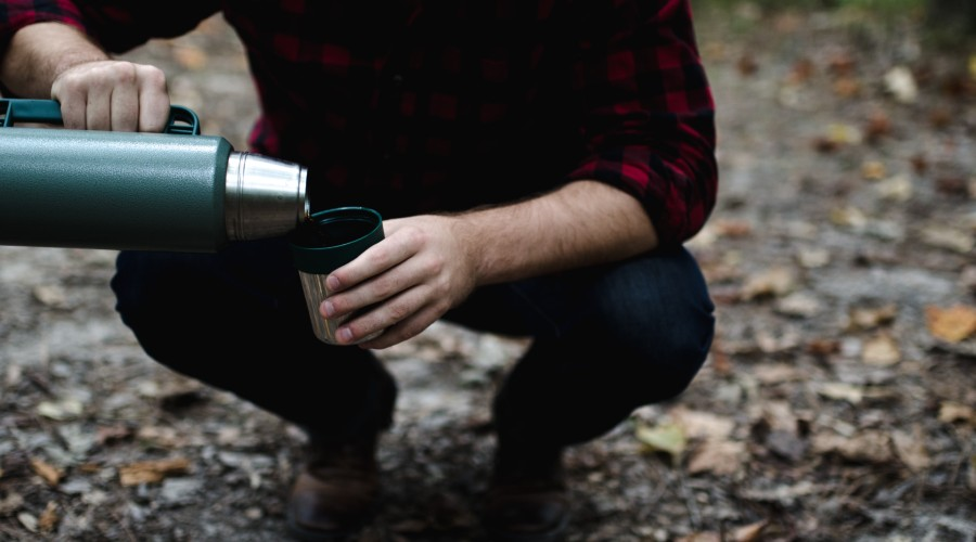 man bending his knees pouring thermos contents in cup