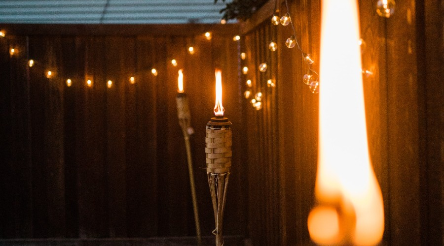 lighted candles along fence during night time