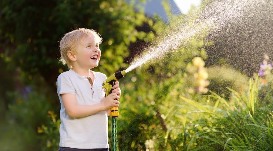 young boy holding the sprayer end of a garden hose, watering the garden