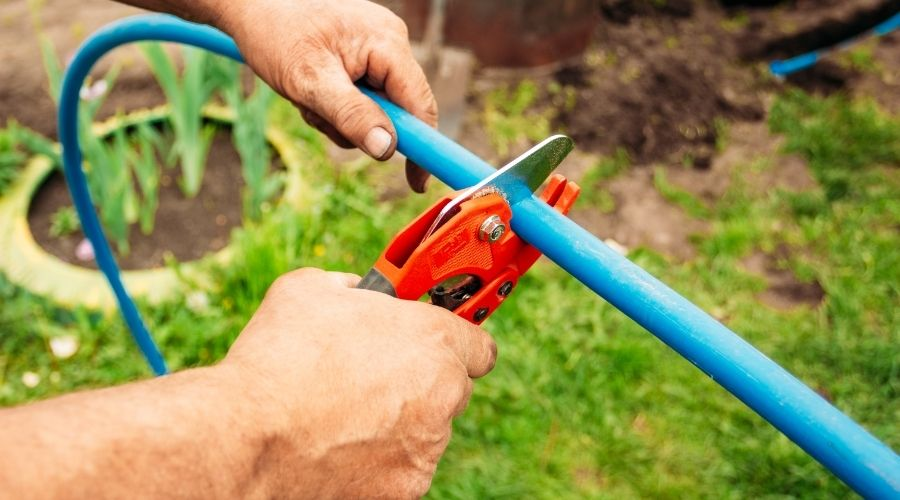a person cutting a blue garden hose outside in the grass