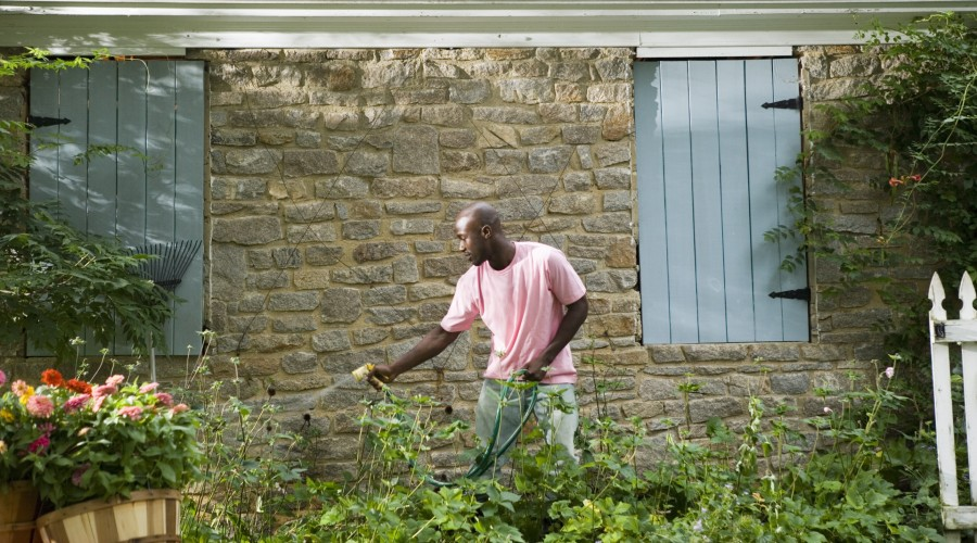 a man outside watering his garden with a hose