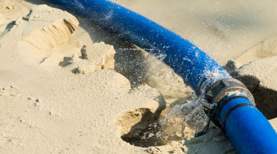 a blue garden hose leaking on a surface of sand