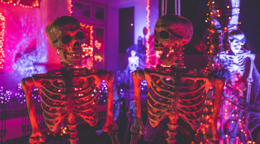 skeleton decorations in front of a house, lit up by red lights