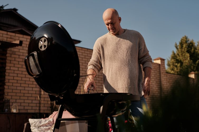 Man grilling in his backyard
