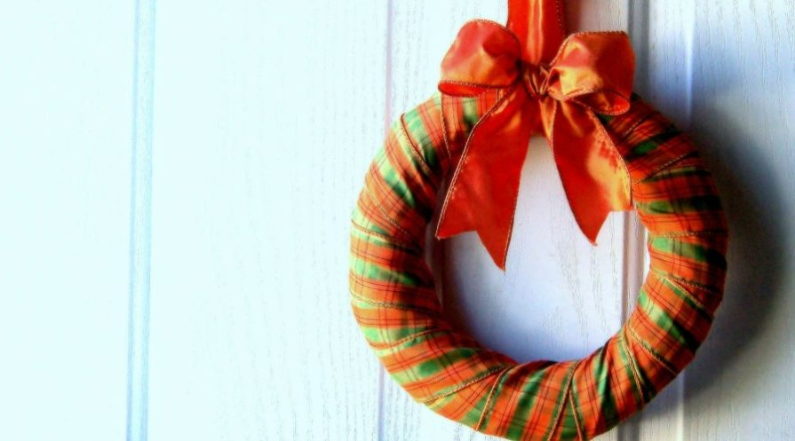 ribbon wrapped wreath on blank white door